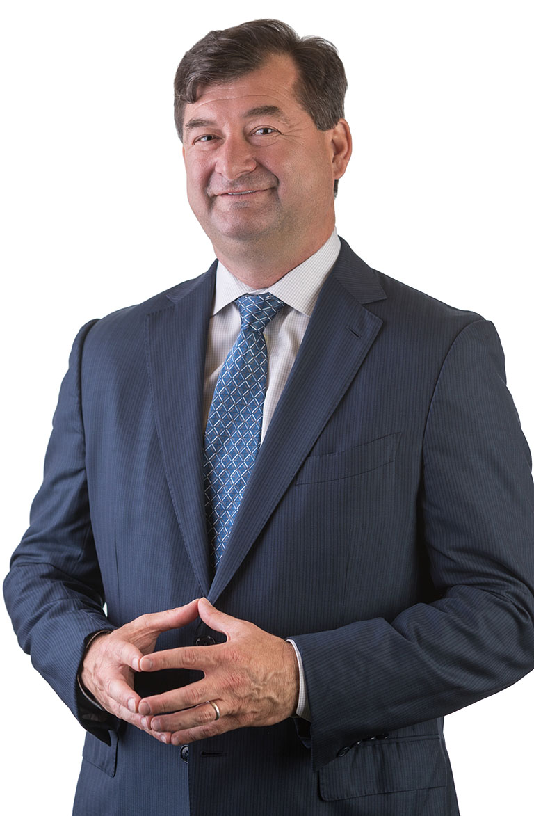 A lawyer named Brian Aylstock wearing a suit with a blank background looking into the camera.
