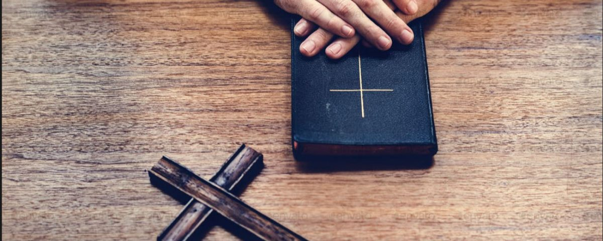 A Person with a bible and a wooden cross on a table.