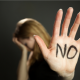 "A photograph of a woman blurred holding her head in her hand, while her other hand is raised up with marker written on it stating, ""NO."""