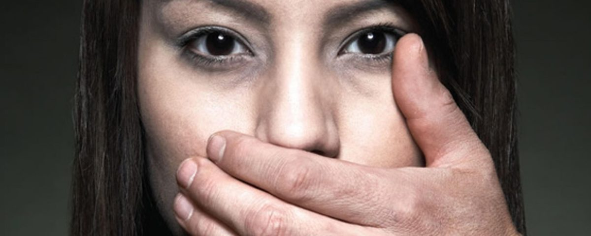 A photograph of a woman with a hand covering her mouth.