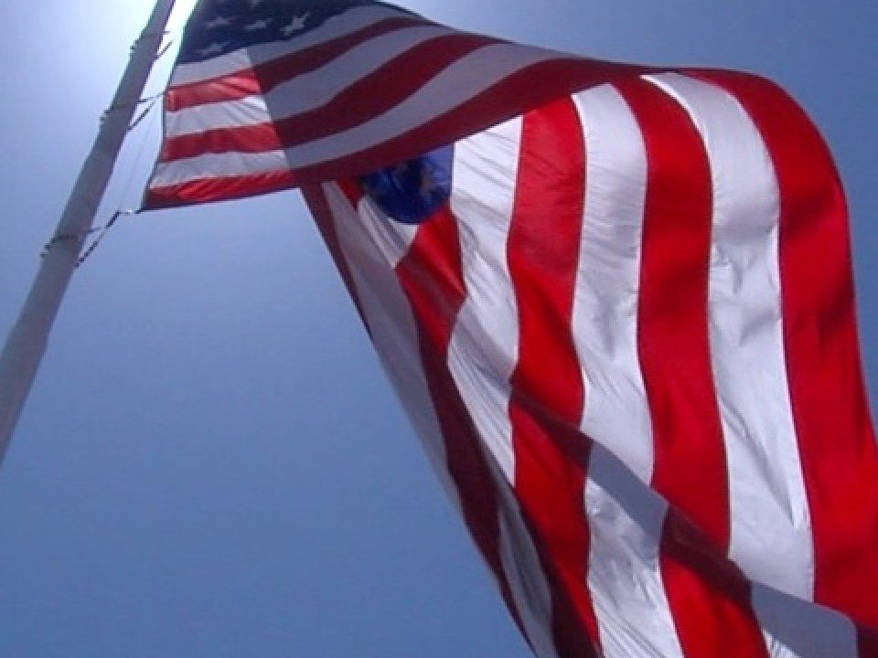 American Flag blowing in the breeze over a clear blue sky.