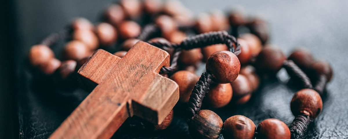A photograph of rosary beads with the cross. The beads & cross are a red wood with the twine lacing them together. The twine is a deep brown that braids around the beads.
