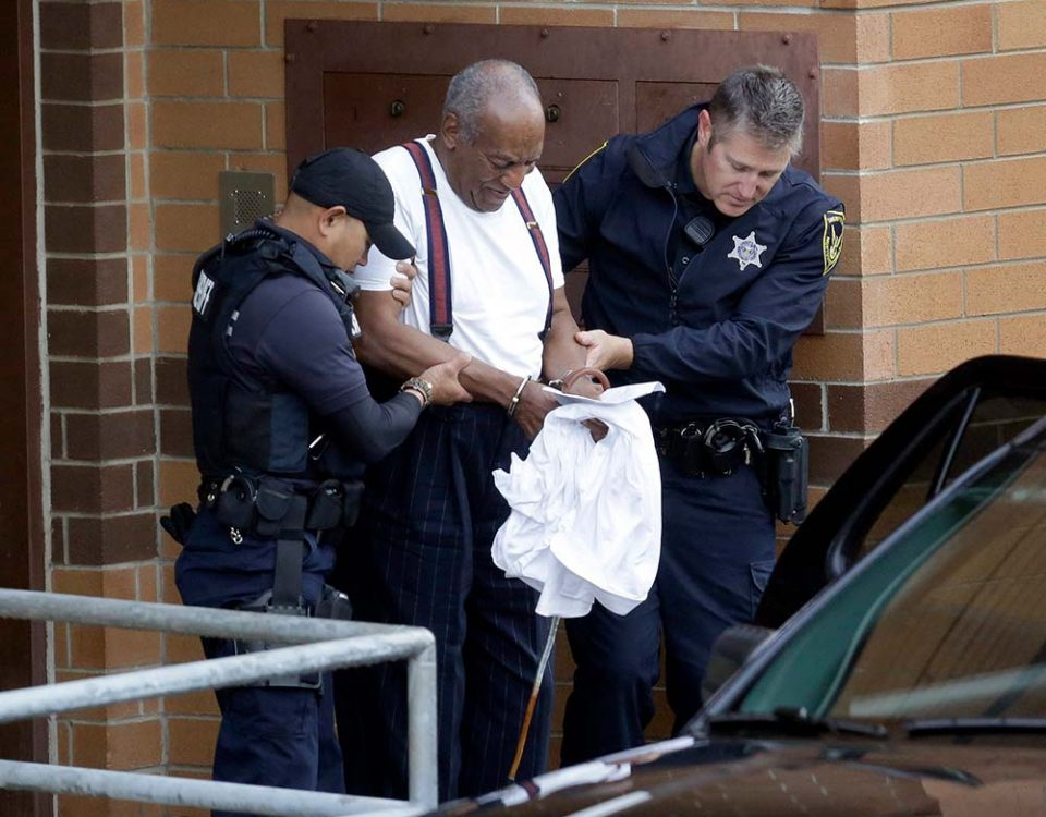 Bill Cosby, a famous comedian, is being escorted towards a vehicle in handcuffs by police officers.