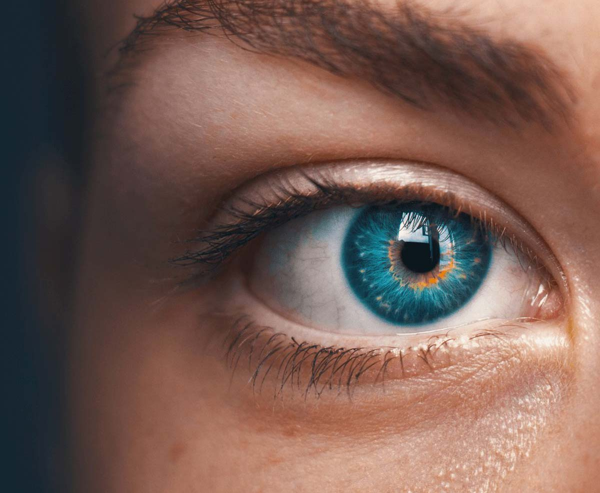 A close up shot of a persons eye & eyebrow. The eye is bright turquoise and orange, and the light is reflecting off of the iris.