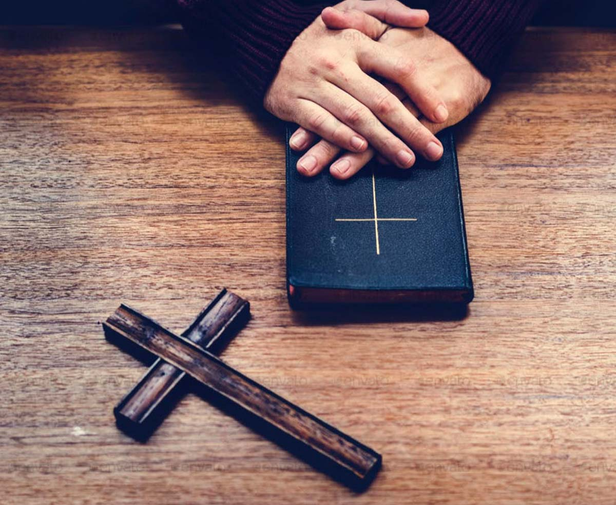 A wooden table with a pair of hands laid over the Bible, and a cross is laying on the table next to the Bible.