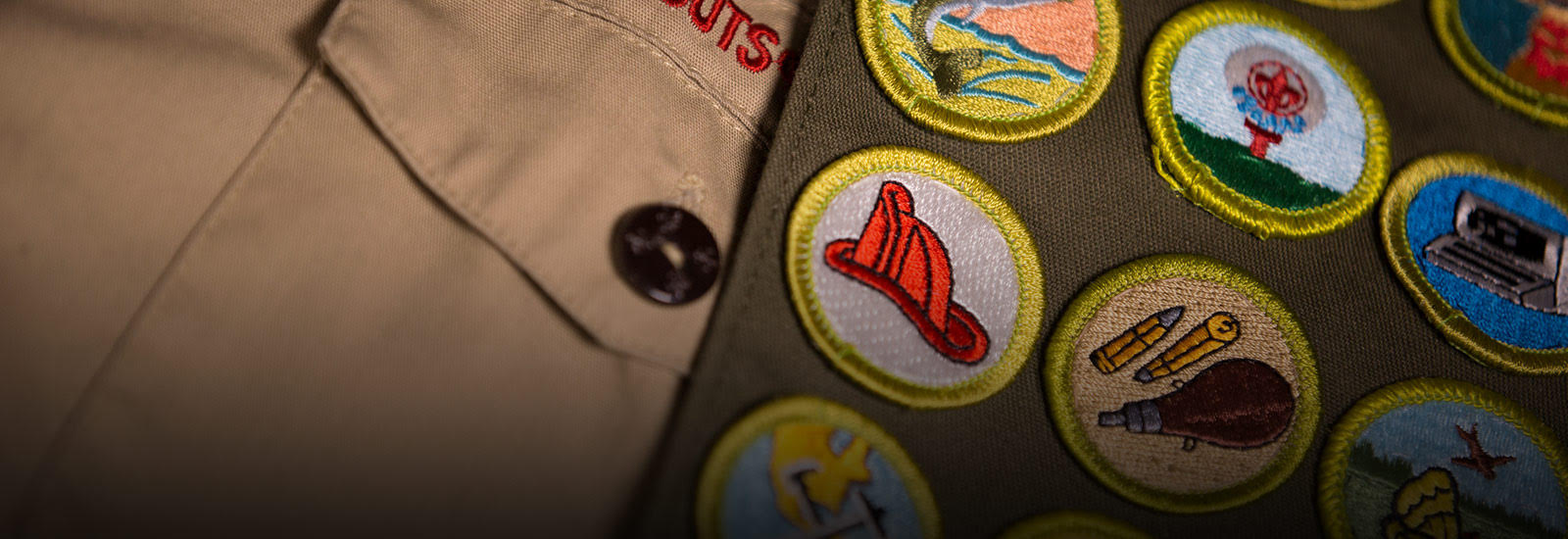 Close up of Boy Scout uniform, showing the badges sewn into the sash. The name Boy Scout can clearly be seen, with a fireman helmet badge as the most visible badge being displayed.